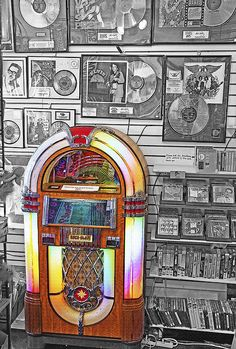 "A still life image inside a tourist memorabilia shop in South Dakota. A lighted, vintage Rock-Ola jukebox sits amongst music industry memorabilia and keepsakes. On the wall are framed gold records of such classic bands and musicians as Elvis, Beach Boys, Buddy Holly, The Beatles and Aerosmith. There are also shelves of old CD's, DVD's and VHS tapes, containing nostalgic TV shows, movies and music. A nostalgic still life depicting ""the good old days""."