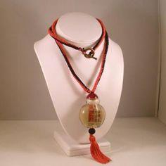 Collar con nudos de serpiente en dos colores, rojo y negro a lo largo de todo el cordón. Colgante hecho con una botella china rematada con nudos de botón, una cuenta de resina y un pon pon rojo.