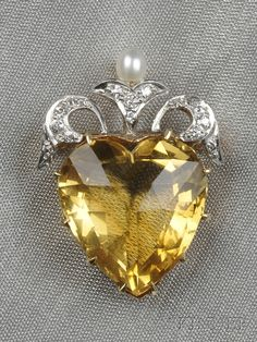 Edwardian Citrine and Diamond Heart Pendant/Brooch, the faceted citrine heart with old single-cut diamond melee ribbon surmount, platinum-topped 14kt gold mount, lg. 1 in.