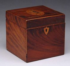 INLAID SQUARE TEA CADDY. The fine mahogany square box having a hinged cover and open interior. The cover with oval bird on branch inlay with a lined border, nice mahogany veneers and having a shield escutcheon. Key present. Circa 1800. James D. Julia Inc.