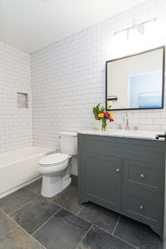 White subway tile with gray grout, slate quartzite floors, modern gray vanity with Carrara Marble vanity top.