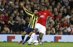 Manchester United's record signing Pogba manoeuvres the ball away from Fenerbahce's Alper Potuk during the encounter