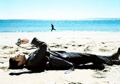Joseph Gorden-Levitt... in a suit on the beach.. with a camera... and a jogger.. arty.