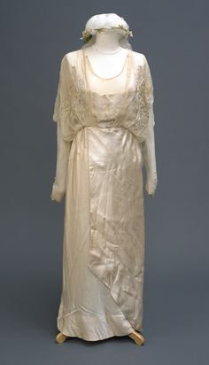 ca 1918 A Madame Clapham wedding dress. Cream net veil with artificial flower bud wreath, cream silk stole with weight at back of neck, embroidered with theatre masks, dress cream silk, chiffon arms and across bust, theatre masks embroidered across bust, front fastening.
