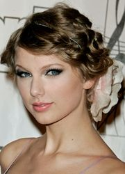 taylor swift curly updo hairstyle with side parting and flower hair accessory