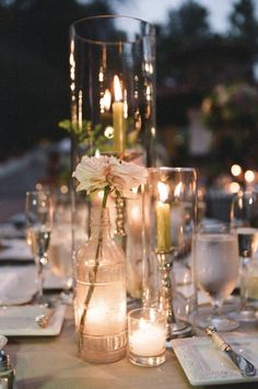 Wedding candlescape idea - using clear glass bottles and vases #weddingcandleideas #glassbottlecandleholders