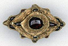 Finger-ring; gold; massive, thick hoop with interlace wire design on the exterior; three tiered lozenge-shaped bezel set with garnets; decorated with wirework and pellets. 15th century. Via Taresa A Secas via Noel P