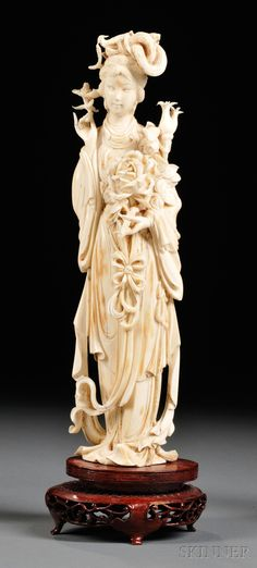 Ivory Carving, China, 19th century, standing figure of a lady holding flowering branches, dressed in draped robes, glued onto stand, ht. 12 in