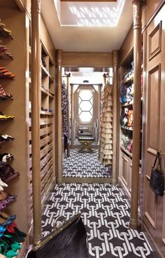 Amazing walk-in closet with white & brown geometric carpet, floor mirror and built-in closet cabinets & shelves.