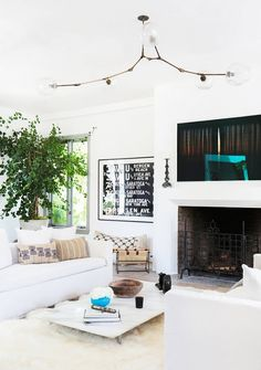 White living space with modern light fixture, fireplace, patterned pillows, and large indoor plant
