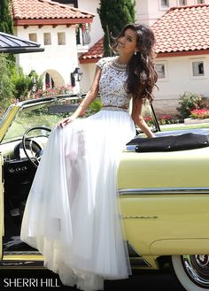 Bask in the beauty of the romantically feminine Sherri Hill 50110 two-piece prom dress with classic A-line silhouette. The crop top is styled in floral lace over a nude lining and showcases a beaded illusion jewel neckline framed with illusion cap sleeves. The illusion and lace back frame a triangular cutout. Tiers of beads accent the waistband of the full-length skirt. It cascades in filmy gathered layers into a dreamy train and features a high-thigh front-side slit.