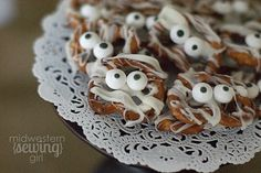 Mummy Pretzels -  An easy Halloween Party snack idea for kids made with pretzel twists, white almond bark and candy eyes. #Halloweenfood #Halloweenparty