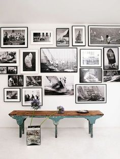 Black and white photos in simple black frames hung low above the rustic blue bench