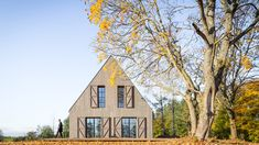 The shutters of this Lithuanian holiday cottage can open to transform the completely closed gabled volume into a bright space with views of the nearby lake.
