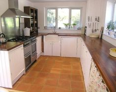 photo of farmhouse kitchen beige pink white kitchen with belfast sink quarry tiles wooden worktop and range cooker