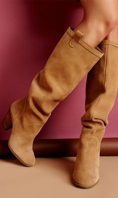 Soft suede and slouchy knee-high boots with a rounded toe, stacked heel and pull on tabs. Unlined for that effortlessly slouchy silhouette.
