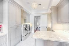 Expansive laundry room with plenty of storage and granite top counter for folding.