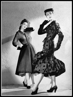 Model on left in pleated mousseline dress by Christian Dior, model on right in black satin dress with appliqued velvet circles by Balenciaga | Photo:  Jacqued Decaux, 1950
