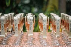 scroll escort cards on pink champagne glass and sequin tablecloth