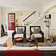 This is a living room - but I would love to do this on the porch / entryway. Paint out front door red,  accent the wicker chair and bench with white and black pillows, fill our white flower pots with red geraniums, etc.