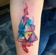 Watercolor inspired Triangle Glyph Tattoo. As the symbols are being drawn within the triangle, you can see that the colors are slowly spilling out of it as if overflowing throughout the boundaries. The watercolors also help add a soft touch to the design.