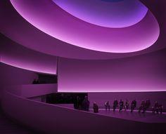 l'interno del museo Guggenheim di New York illuminato da luci led colorate durante un installazione artistica