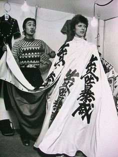 David Bowie with fashion designer, Kansai Yamamoto, 1973. I've been laughing at this forever, please help.