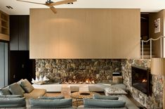 contemporary living room with stone and wood fireplace