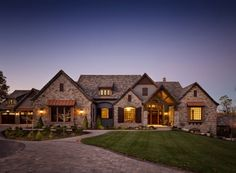 Western Estate Custom Home - Front Elevation at Night: Grand western estate with natural stone, copper, and natural wood accents. Custom home design accented by custom lighting makes a statement at night. Custom Home Plans, Custom Home Designs, Custom Home Builders, Custom Homes, Rustic Houses Exterior, Modern Farmhouse Exterior, Dream House Exterior, Colonial Exterior, Bungalow Exterior