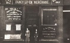 Two women outside Abraham Links drapery shop in Main Street in the Gorbals, 1907. The top left hand window has lettering in Yiddish while the bottom right window has a similar message in English. Abraham Links (1886-1953) was a leading figure in the Zionist movement in Glasgow.