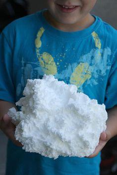 Un garçon qui tient un nuage de savon