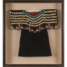 """'Yakima Beaded Toddler's Dress 17"""" long, 18"""" wide at yolk. Trade wool dress with floral cotton lining. Yolk is covered with 159 cowrie shells on front. Decorated with trade beads and early 20th century dimes and thimbles. Shadowbox framed and ready to hang.  (est. $2,000-3,000)"""