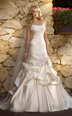 Layers and layers of lavish Dolce Satin make this designer wedding gown a must. The gown's exquisite Lace bodice is sophisticated and flattering on every figure. Delicate pickups in the skirt draws dramatic attention to the gown and the bride wearing it.