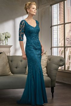 Jade Couture. Netting/Lace with Stretch lining dress with a flare skirt and long, fitted sleeves - all in the color new teal.  Plus Size Available.