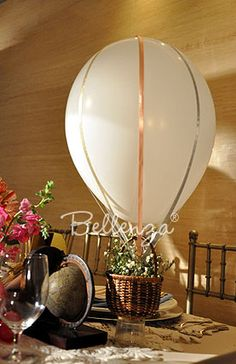 The other DIY decor elements are the hot air balloon centerpieces. Simply assembled from pastel-colored balloons, pink and blue ribbon, and small baskets filled with baby's breath, these accents bring in the vintage-travel theme in a totally doable way!