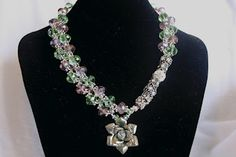 Unique asymmetrical intertwined design with translucent green and purple sparkling crystal and Rhinestone encrusted charms and a delightful rose pendant reminiscent of a bygone era. Green And Purple, Charms, Jewelry Making, Sparkle, Crystals, Pendant, Rose, Unique, Design