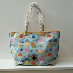 Dooney & Bourke Cupcake Leisure Shopper Dooney & Bourke Cupcake Leisure Shopper.  Light Blue.  Measures 18 inches across the top, 11 tall, and 7 deep.  Comes with registration card,  but no bag. No flaws. Dooney & Bourke Bags
