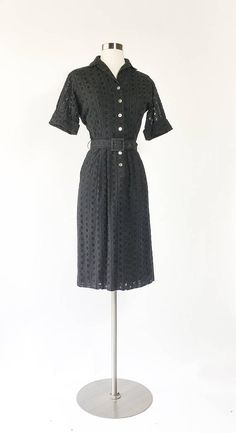 ◾️ Black cotton eyelet lace, the cutouts look like wagon wheels or lemon slices. Collar. Button front. 3/4 cuffed sleeves. Sheath shape. Matching belt. Lined in sheer cotton. No stretch. Good vintage condition, with no visible flaws or issues noted. ◾We only have ONE of each item, we dont have extras or other sizes!  B U S T: 36  W A I S T: 26  H I P S: 38  S H O U L D E R S: 17  S L E E V E S: 9  I N S E A M: -  L E N G T H: 40  B R A N D: Made in California By Shirt Dressed Inc.  F A B...