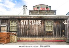"""OSAKA, JAPAN - JUN 2, 2015 : Photo of a building called """"STOCTANE"""" with wooden boxes in the front that located inside Universal Studio, Osaka, Japan. Replicated in Cowboy Wild West Theme. - stock photo"""