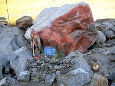 Kedarnath This large rock, now called the Divya Bhim Shila (Divine Bhim Stone), has become a small shrine in its own right, to mark what is largely viewed as a miracle.  The side of the rock has been smeared with the red powder known as sindur, and the decorated trident placed to one side.    Bhima was one of the five Pandava brothers in the epic Mahabharata, and since he was known for his prodigious size and strength, this seems an appropriate identification with this stone.