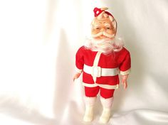 Vintage plastic Santa doll is wearing traditional red and white outfit made from cotton fabric (maybe hes from the South Pole!). His beard is kind of like Barbie hair. His arms are articulated so you can move them, and his boots removable. His white plastic belt is taped in the back, but I believe thats the way he was made. The arms are a different kind of plastic (harder) than the face.  He is 9 inches (23 cm) tall.  Condition: Very good. Someone made this into an ornament my stringing red…