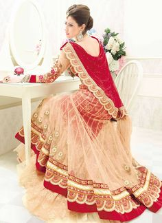 This beige and red colored net lengha is gorgeous!
