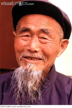 Chinese man. (Portrait of old Chinese man with wispy bear, wearing a Mao-style jacket and cap. China.)