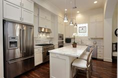 Pretty, antique-style barstools give delicacy and a hint of Old World elegance to this all-white kitchen. The stainless steel appliances and pendant light play off the weathered wood finish.
