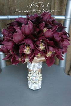 Nisie's Enchanted, Vintage elegance with deep burgundy cymbidium orchids with a ivory ribbon wrap, with rhinestone top and bottom banding with broach.