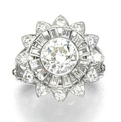 DIAMOND RING, ALEXANDRE REZA Of stylised flower head design, centring on a collet-set circular-cut diamond, within a radiating surround of baguette and brilliant-cut stones, size M, French assay and maker's marks for Alexandre Reza.