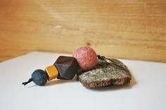Schlüsselanhänger mit Filzkugeln in den Farben altrosa und anthrazit, selbstbemalte und matt lackierte Holzperle in goldfarben (mit Acrylfarbe bemalt) und geometrischer Holzperle in dunkelbraun. Farblich passend dazu ein bronzefarbener Schlüsselring. Aufgefädelt auf eine schwarze Kordel. Dieser Schlüsselanhänger hat eine Länge von ca. 10,5 cm.