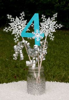 Esse modelo de Centro de mesa está mais simples porém muito bonito para você usar na sua Festa Infantil Frozen. Destaque para o efeito do gliter no vidro reciclado e da idade da aniversariante. Fonte da imagem Catch My Party.