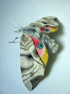 Made of cotton, fake fur, fabric paint, embroidery thread, wire, textile moths by Yumi Okita.