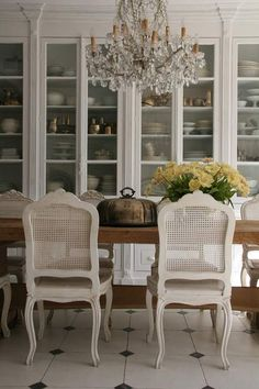 Same rough table offset against French chairs, floating chandelier & crisp white tile floor. LH